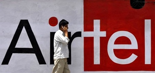 8052-a-man-talks-on-a-mobile-phone-in-front-of-a-bharti-airtel-ad