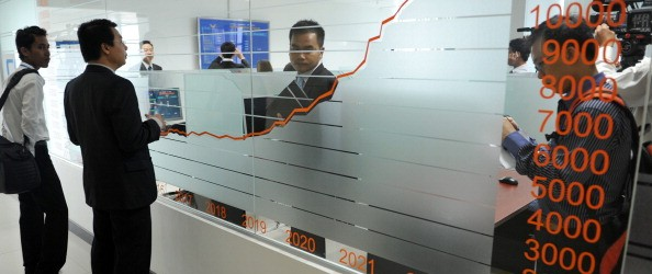 People stand near a stocks graph during launching ceremony at the Cambodian Securities Exchange (CSX)