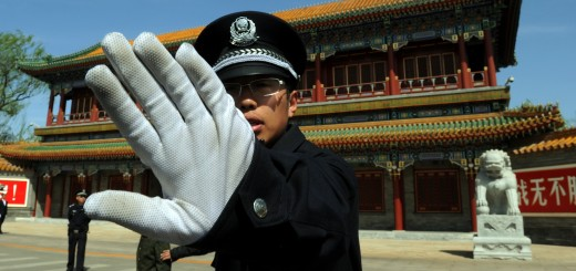 A Chinese policeman blocks photos being