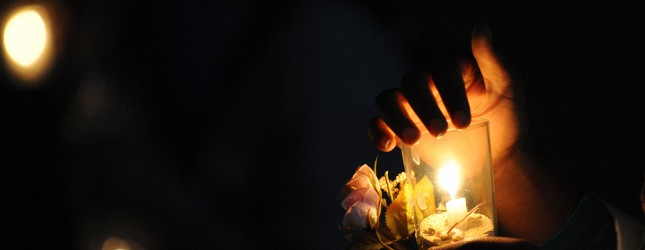 A Libyan woman holds a candle during a c