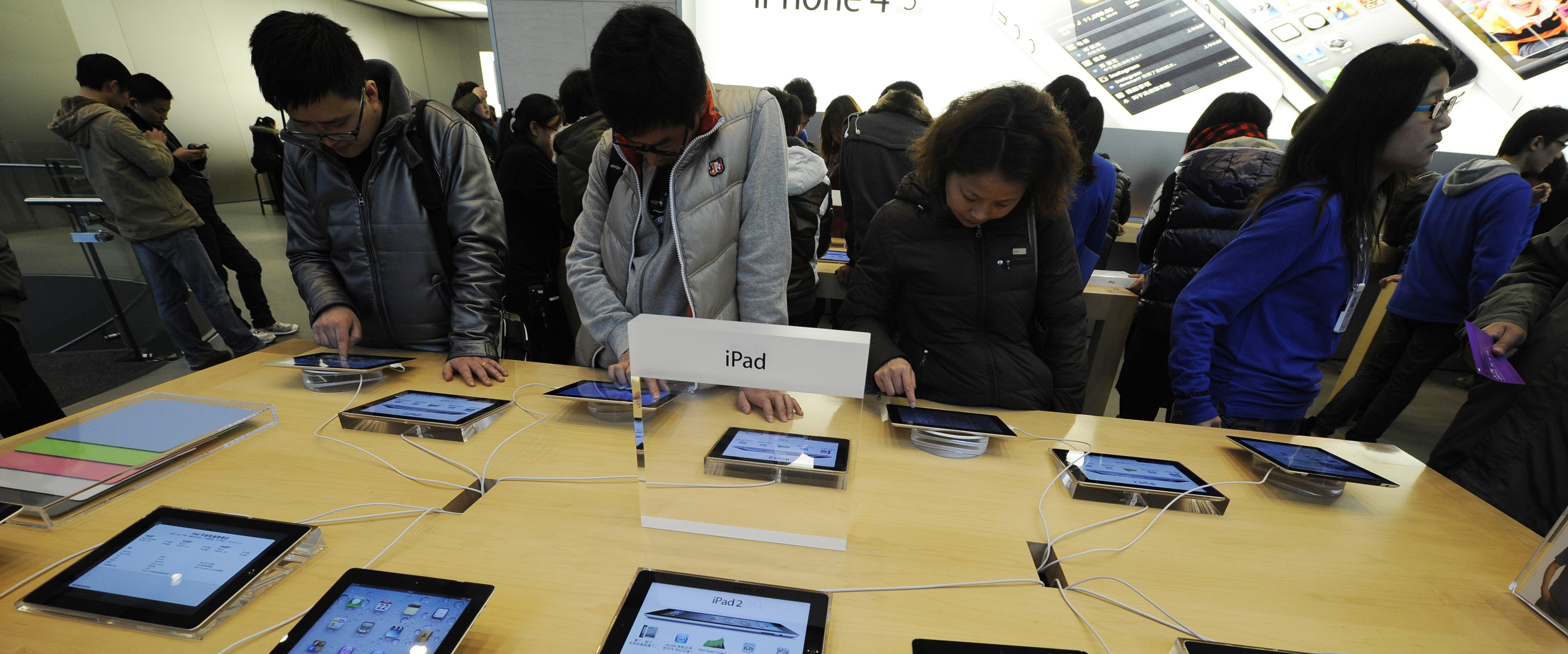 Customers look at Apple iPads at a store