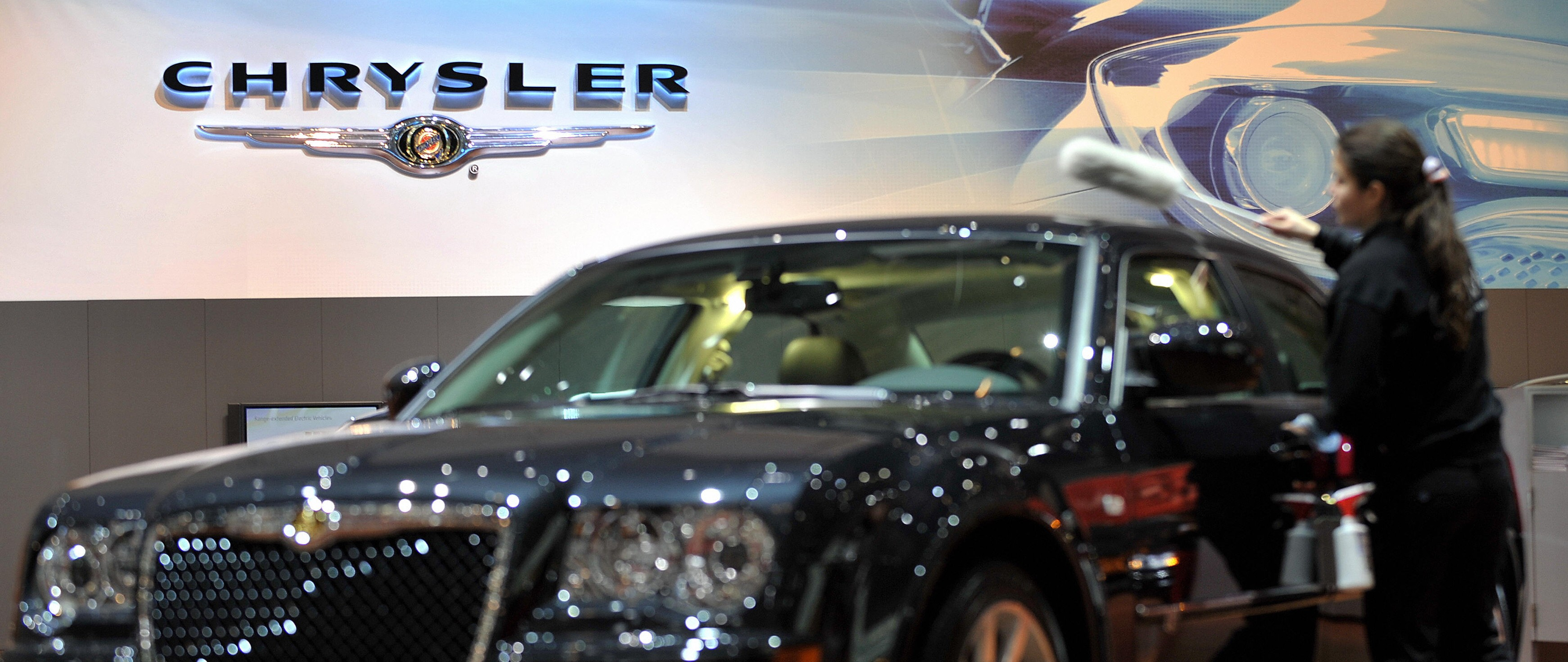A cleaner wipes a car at the Chrysler bo