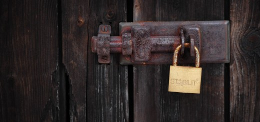 A padlock closes a wooden door at a grav