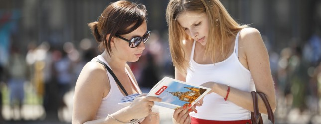 Tourists use a guide book of London near