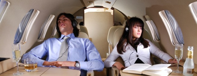 Young business couple sleeping and enjoying the flight in the small private airplane.